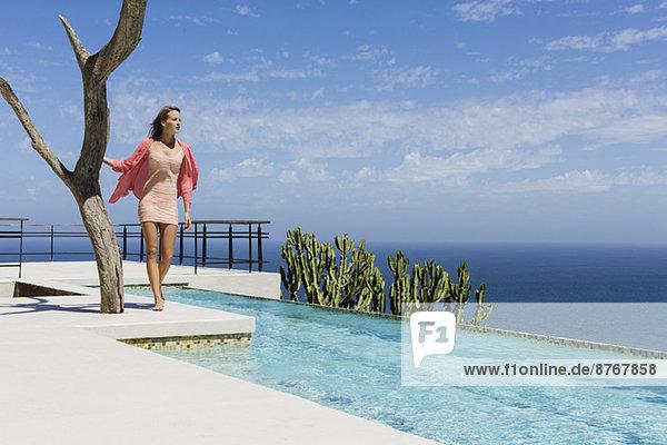Frau steht am Pool mit Blick auf den Ozean