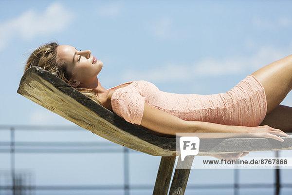 Frau im Kleid Sonnenbaden auf dem Sessel