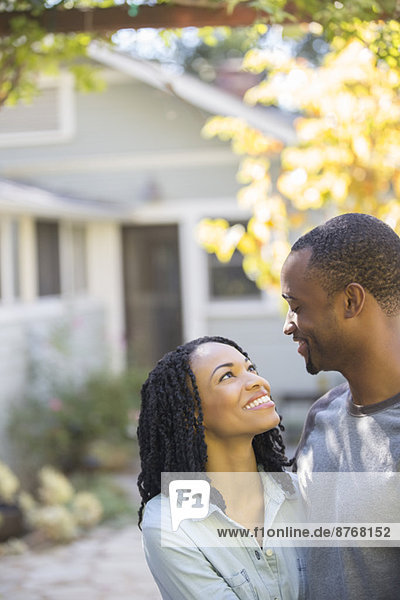 Glückliches Paar  das sich vor dem Haus umarmt.