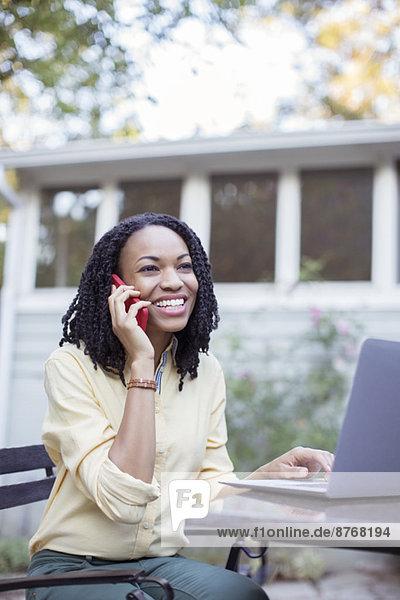 Glückliche Frau beim Telefonieren am Laptop auf der Terrasse