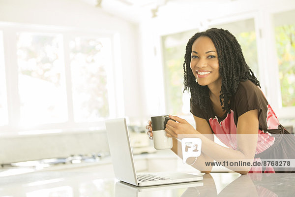 Porträt einer lächelnden Frau beim Kaffeetrinken am Laptop in der Küche