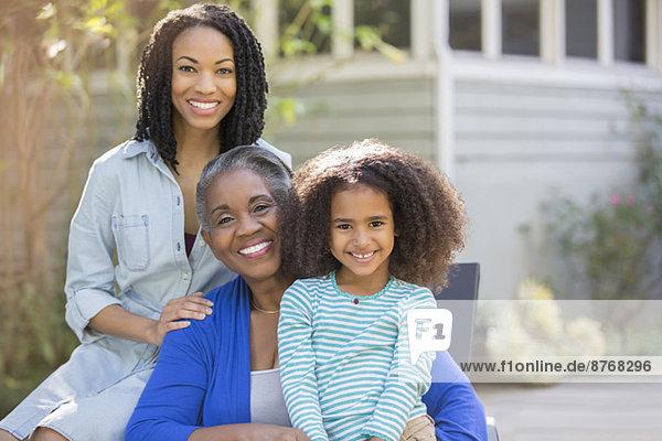Porträt von lächelnden Mehrgenerationen-Frauen auf der Terrasse