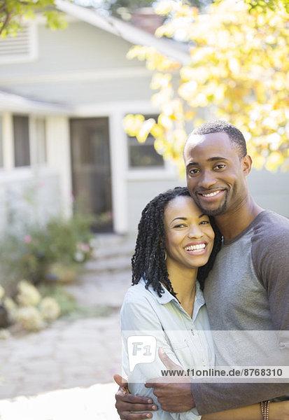 Porträt eines lächelnden Paares  das sich vor dem Haus umarmt.