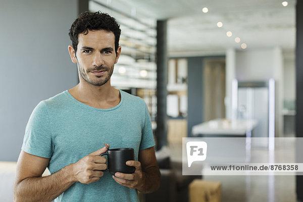 Porträt eines lächelnden Mannes beim Kaffeetrinken zu Hause