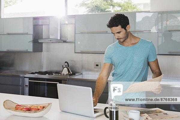 Mann mit Zeitung mit Laptop in der Küche
