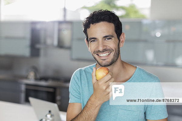 Portrait of smiling man eating apple in kitchen