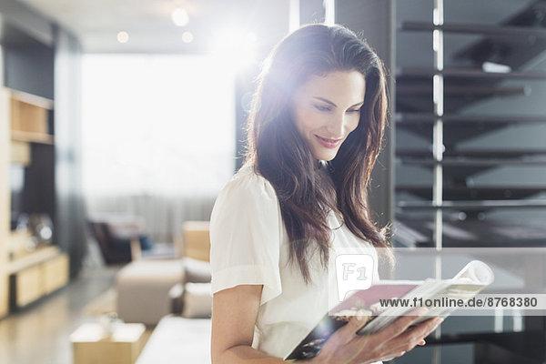 Lächelnde Frau liest Magazin zu Hause