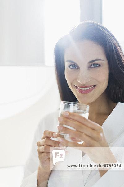 Porträt der lächelnden Frau im Bademantel Trinkwasser