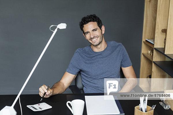 Porträt eines lächelnden Mannes am Schreibtisch im Home Office