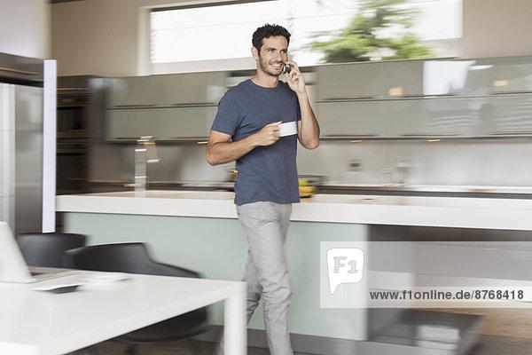 Lächelnder Mann beim Kaffeetrinken und Telefonieren in der Küche