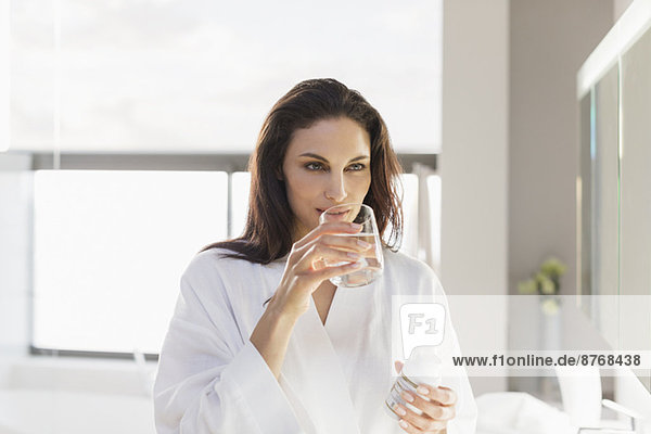 Woman taking medication with water in bathroom