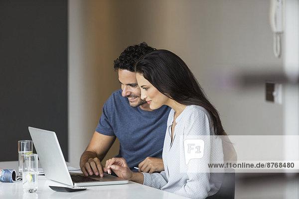 Paar mit Laptop am Tisch