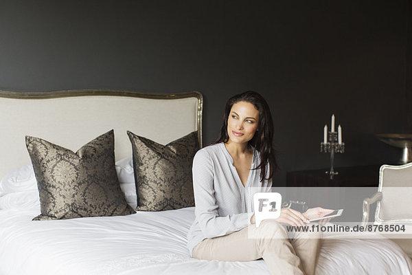 Glückliche Frau mit digitalen Tablette im Schlafzimmer
