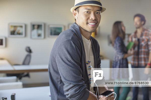Porträt eines gelegentlichen Geschäftsmannes beim Musikhören mit mp3-Player und Kopfhörer