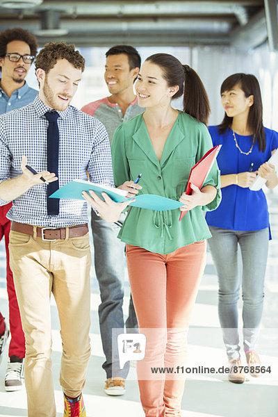 Kreative Geschäftsleute mit Ordnern im Büroflur