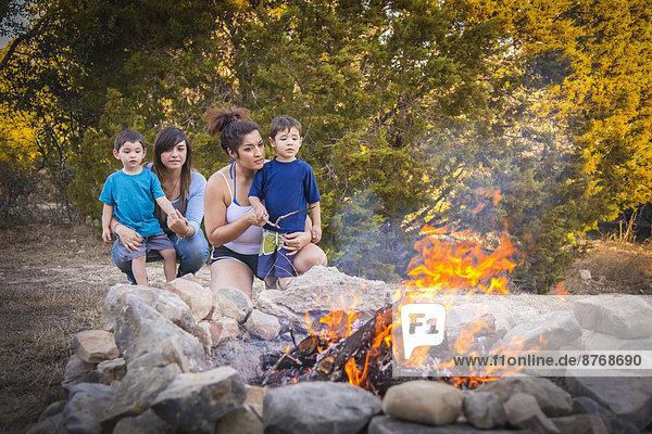 USA  Texas  Zwei junge Frauen und zwei Jungen am Lagerfeuer