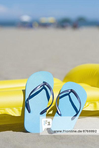 Zwei hellblaue Flip-Flops auf gelbem Luftmatratzenbett am Strand