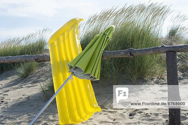 Italien  Adria  Luftbett und Sonnenschirm an Holzzaun an Stranddünen gelehnt