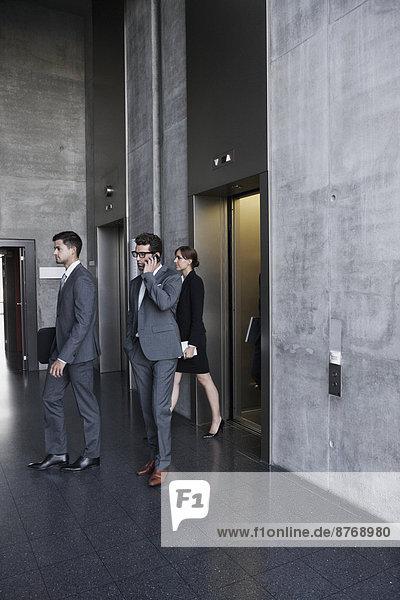 Gruppe von Geschäftsleuten  die den Aufzug verlassen