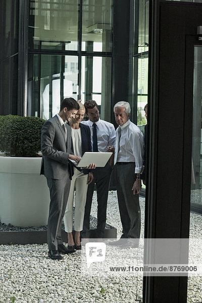 Fünf Geschäftsleute mit Laptop