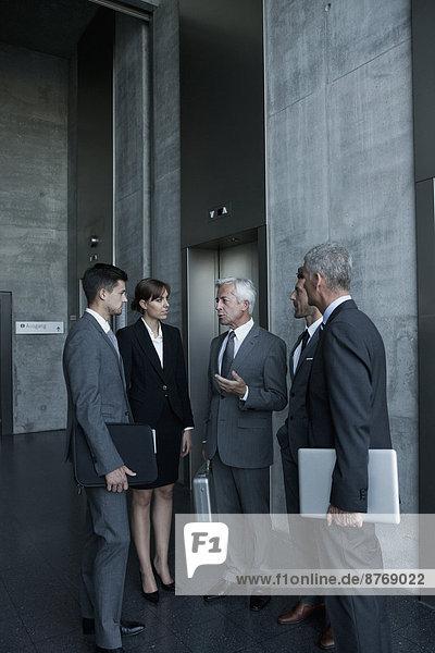 Gruppe von Geschäftsleuten diskutiert am Aufzug