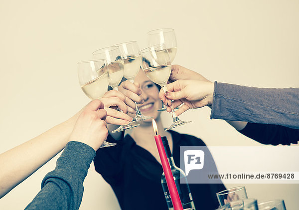 Five young women toasting with wine glasses  partial view