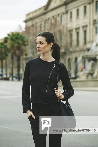 Spain  Catalunya  Barcelona  young black dressed businesswoman in front of a street
