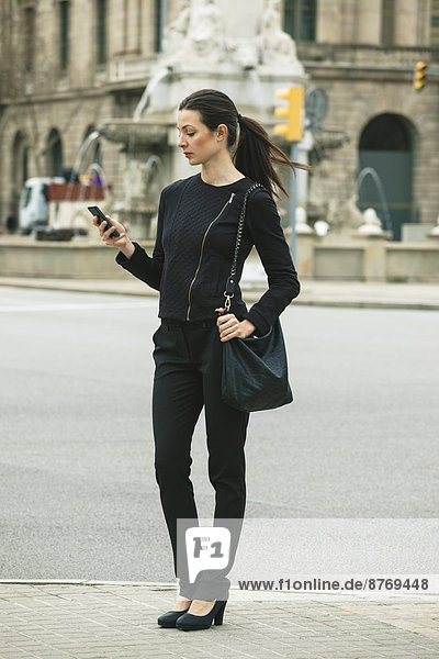 Spain  Catalunya  Barcelona  young black dressed businesswoman looking at her smartphone in front of a street