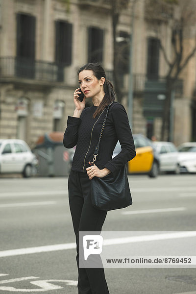 Spain  Catalunya  Barcelona  young black dressed businesswoman telephoning in front of a street