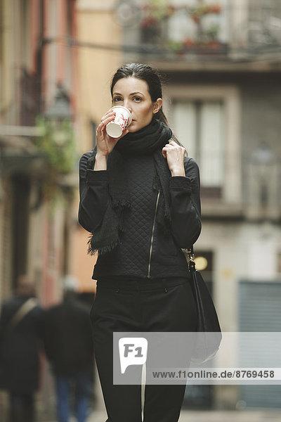 Spanien  Katalonien  Barcelona  junge schwarz gekleidete Geschäftsfrau  die Kaffee trinkt  um vor eine Straße zu gehen.