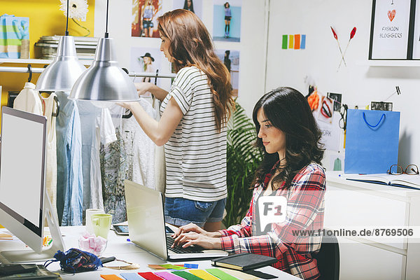 Two female fashion bloggers working in the office