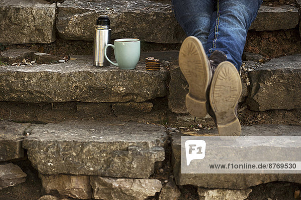 Feet of young man sitting on steps with cup of coffee and thermos flask having a break Feet of young man sitting on steps with cup of coffee and thermos flask having a break