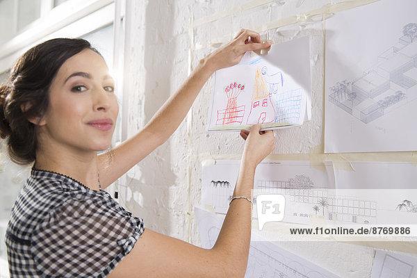 Porträt einer jungen Architektin  die Kinderzeichnungen an der Pinnwand befestigt.