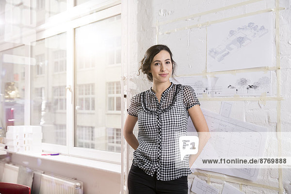 Portrait of young female architect in office