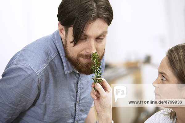 Man smelling at twig of rosemary
