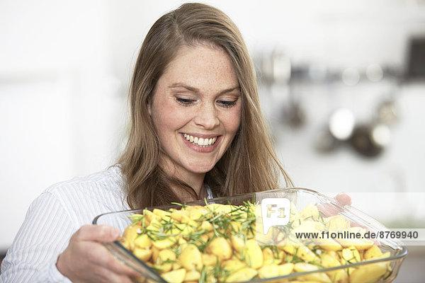 Frau bereitet Kartoffelgratin zu