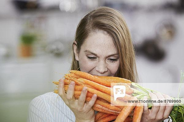 Junge Frau mit Karotten in der Küche
