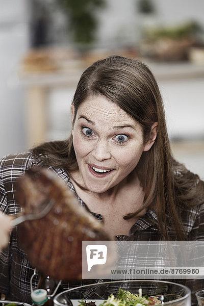 Erstaunte Frau beim Anblick des großen Steaks