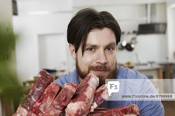 Mann in der Küche mit rohen Steaks