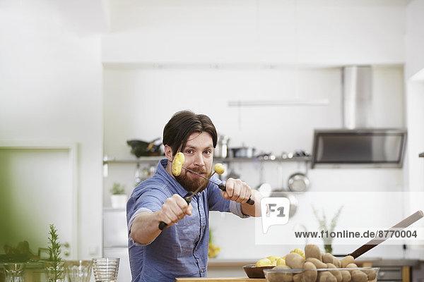 Mann beim Kartoffelspießen in der Küche