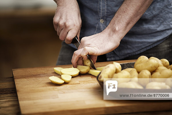 Mann beim Kartoffelschneiden in der Küche