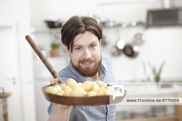 Mann in der Küche hält Pfanne mit Kartoffeln