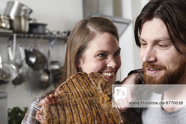 Paar mit großem Steak in der Küche