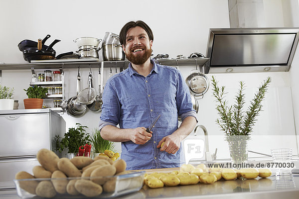 Lächelnder Mann bei der Zubereitung von Kartoffeln in der Küche