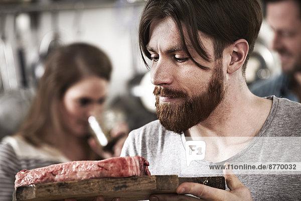 Mann schaut auf rohes Steak auf Schneidebrett