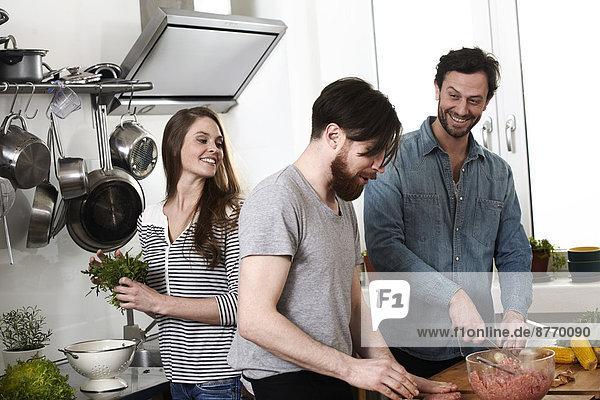 Freunde bei der Zubereitung von Speisen in der Küche