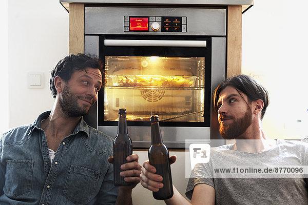 Zwei Männer klirren Bierflaschen am Ofen in der Küche