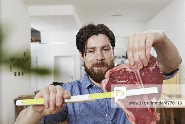 Mann in der Küche mit großem Steak