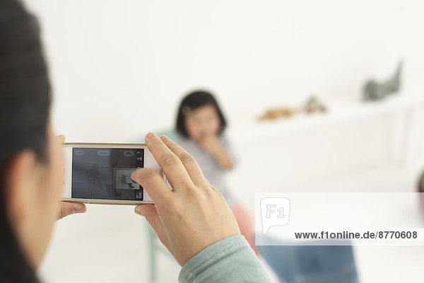 Asiatin fotografiert ihre kleine Tochter mit Smartphone