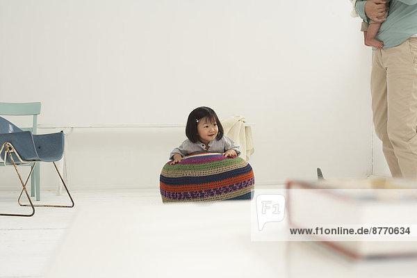 Kleines asiatisches Mädchen  das an einem Sitz hängt.